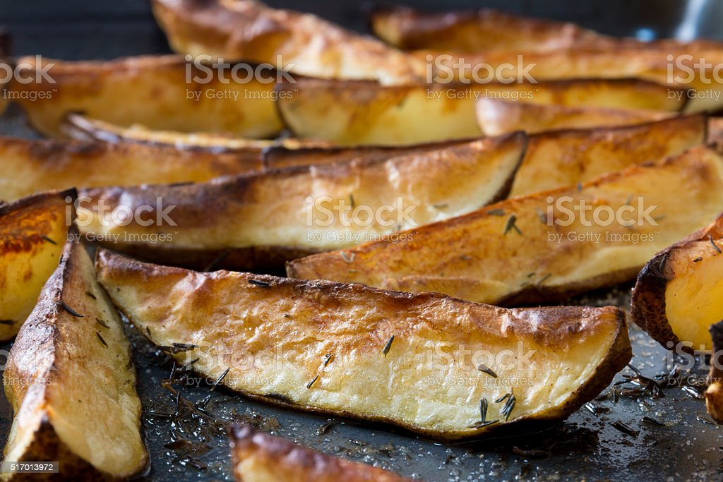 Roasted potato wedges with thyme stock photo