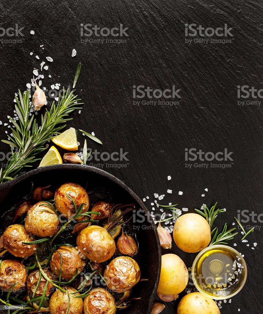 Roasted potatoes on a stone black background stock photo