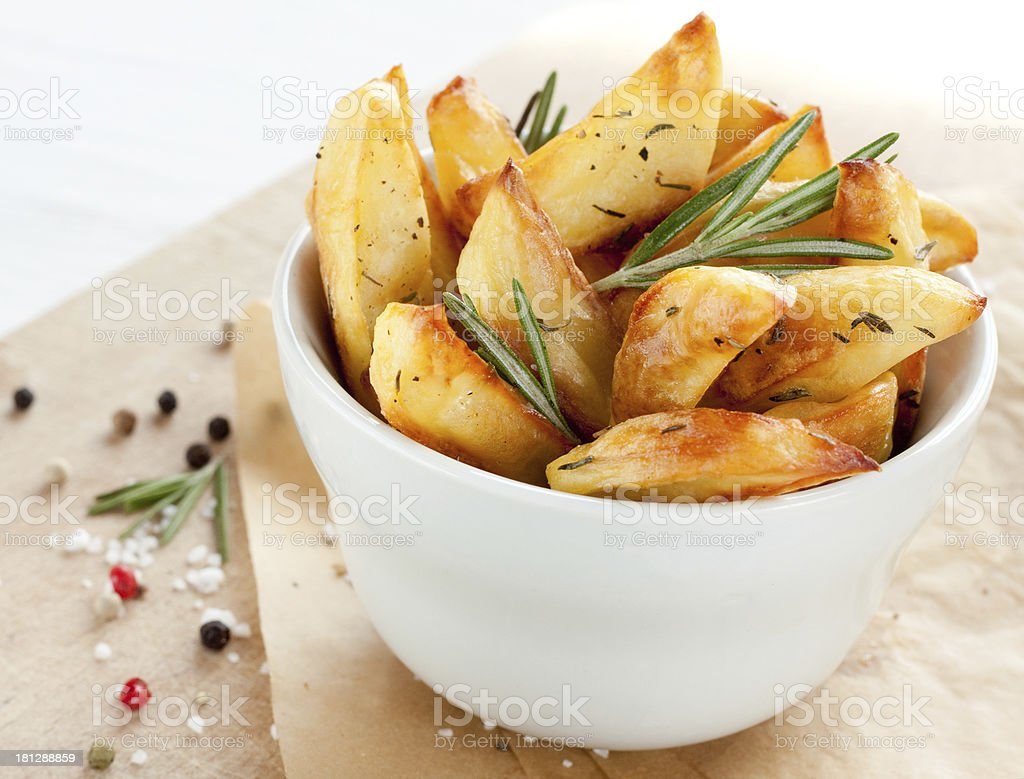 Roasted potatoes with rosemary in a white bowl stock photo