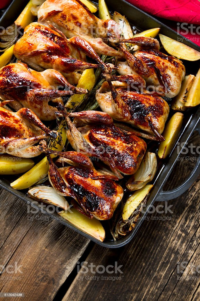 Roasted quails with potatoes, onions and herbs stock photo