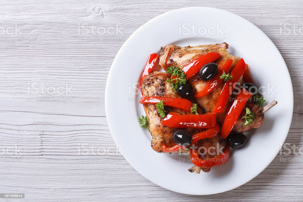 Roasted rabbit leg with peppers and olives top view horizontal stock photo