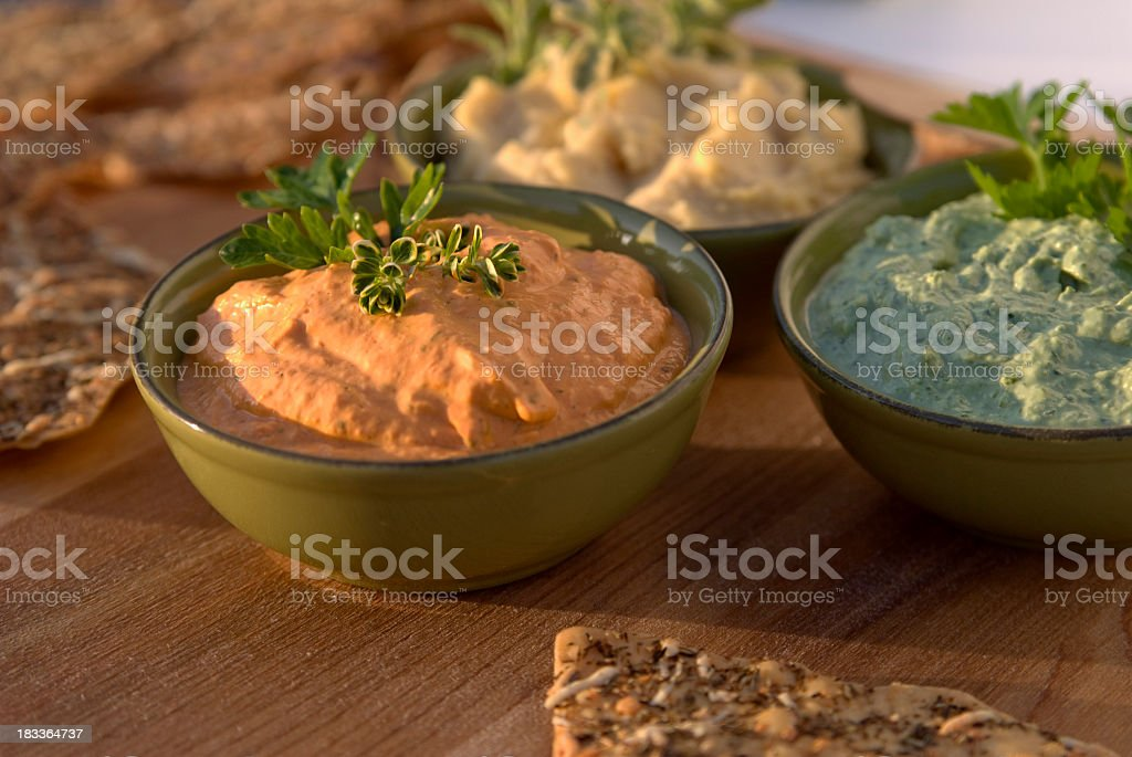 Roasted red bell pepper and vegetable herb hummus on a table stock photo