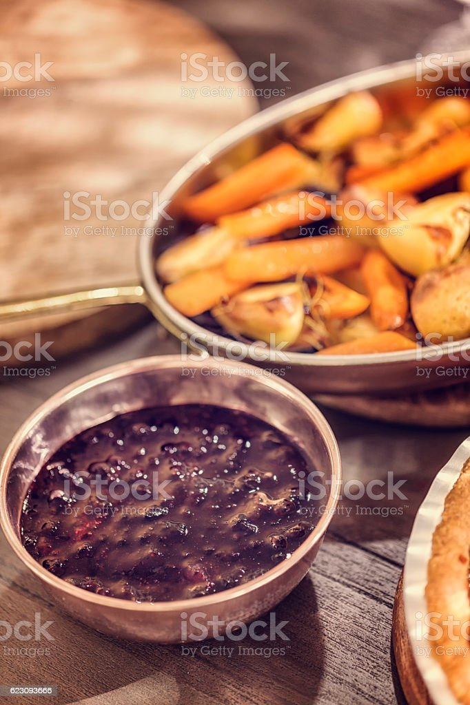 Roasted Root Vegetables and Cranberry Sauce as Side Dish stock photo