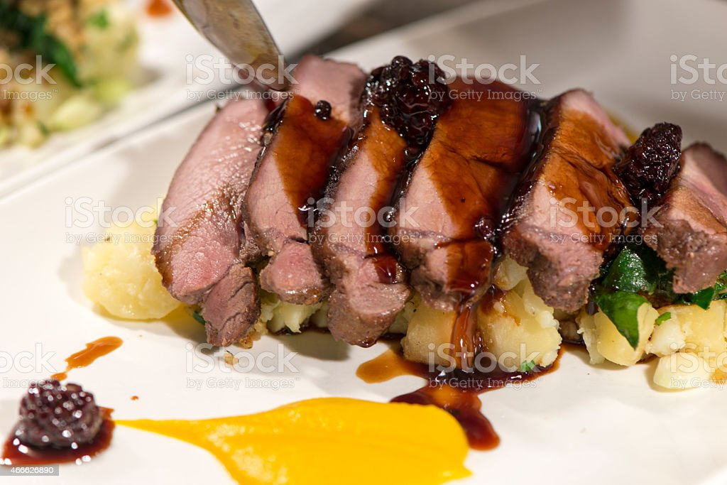 Roasted saddle of boar meat served with potatoes stock photo