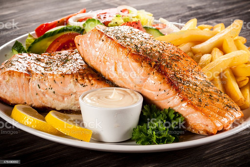 Roasted salmon, French fries and vegetables stock photo