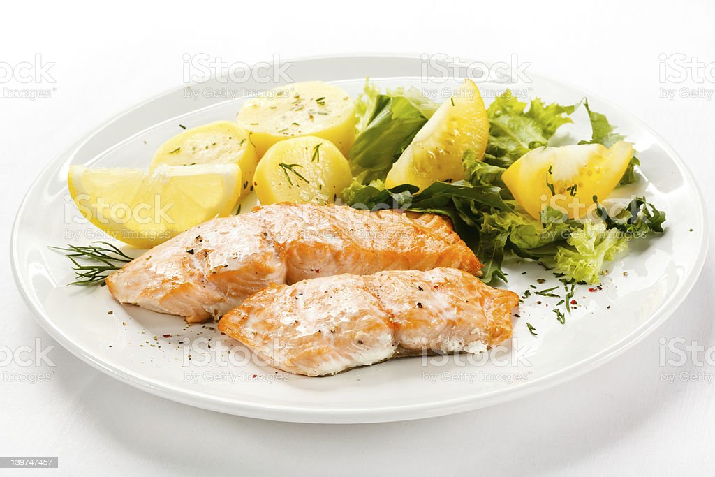 Roasted salmon with lemon slice and yellow tomatoes stock photo