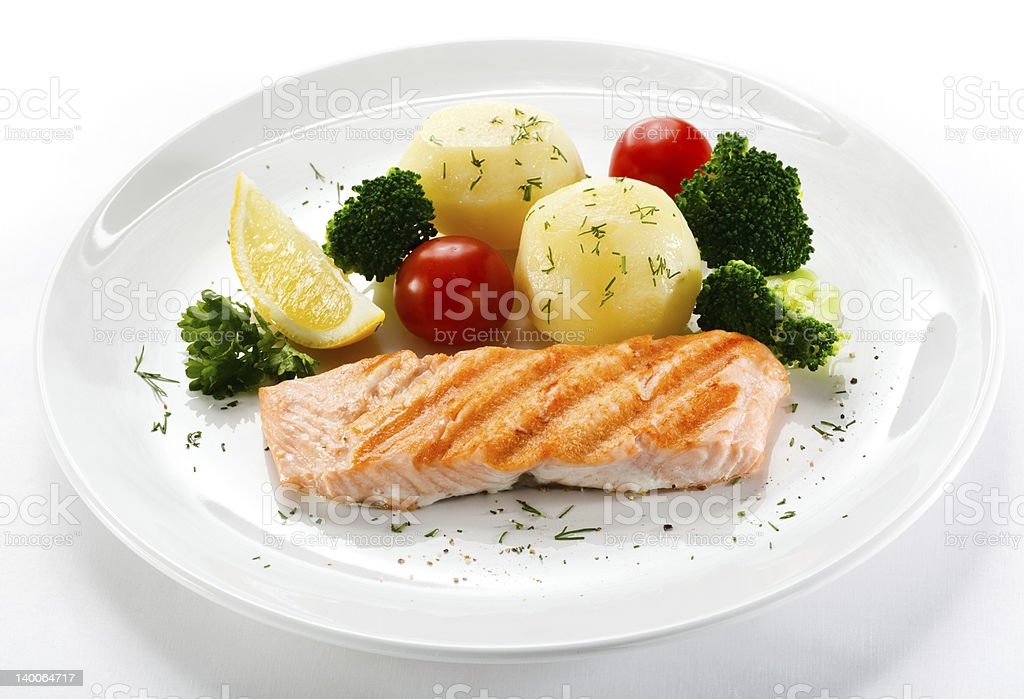 Roasted salmon with vegetables and lemon on a white plate royalty-free stock photo
