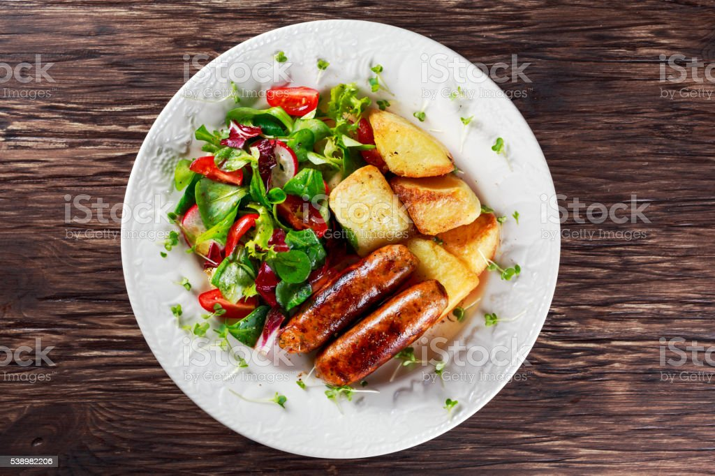 Roasted Sausages with Chips and Mix Vegetable salad stock photo