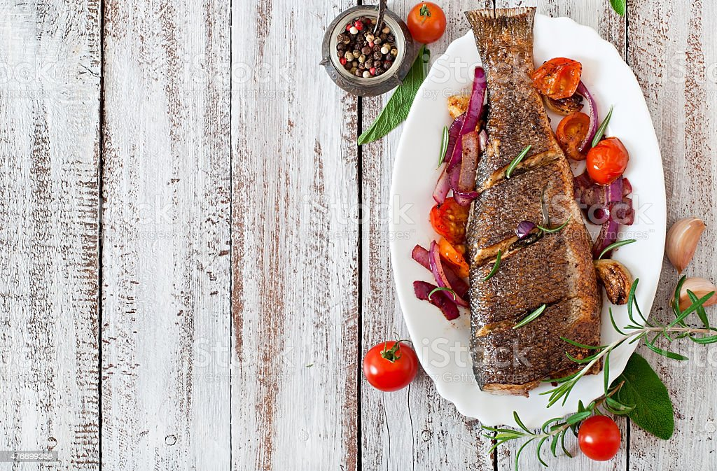 Roasted seabass with vegetables on an old wooden background stock photo