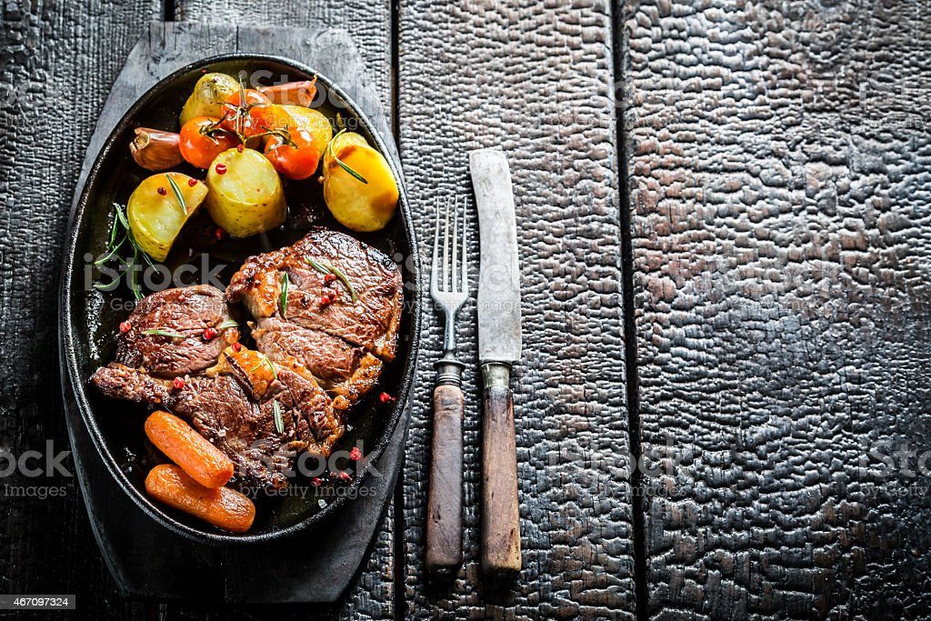 Roasted steak and vegetables with fresh herbs on barbecue dish stock photo