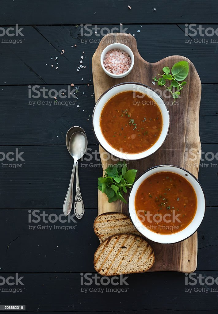 Roasted tomato soup with fresh basil, spices and bread in stock photo