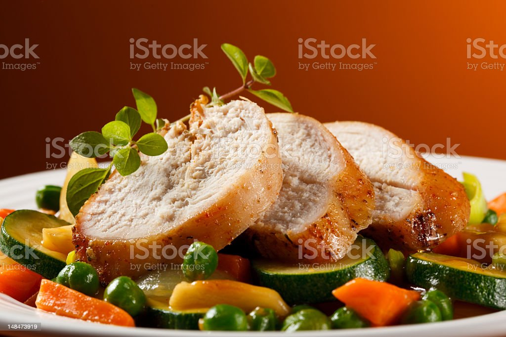 Roasted turkey with vegetables on plate on rust background stock photo