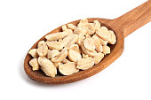 Roasted unsalted shelled peanuts on wooden spoon