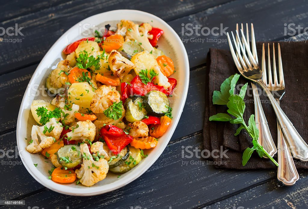 roasted vegetables on an oval dish on dark wooden background stock photo