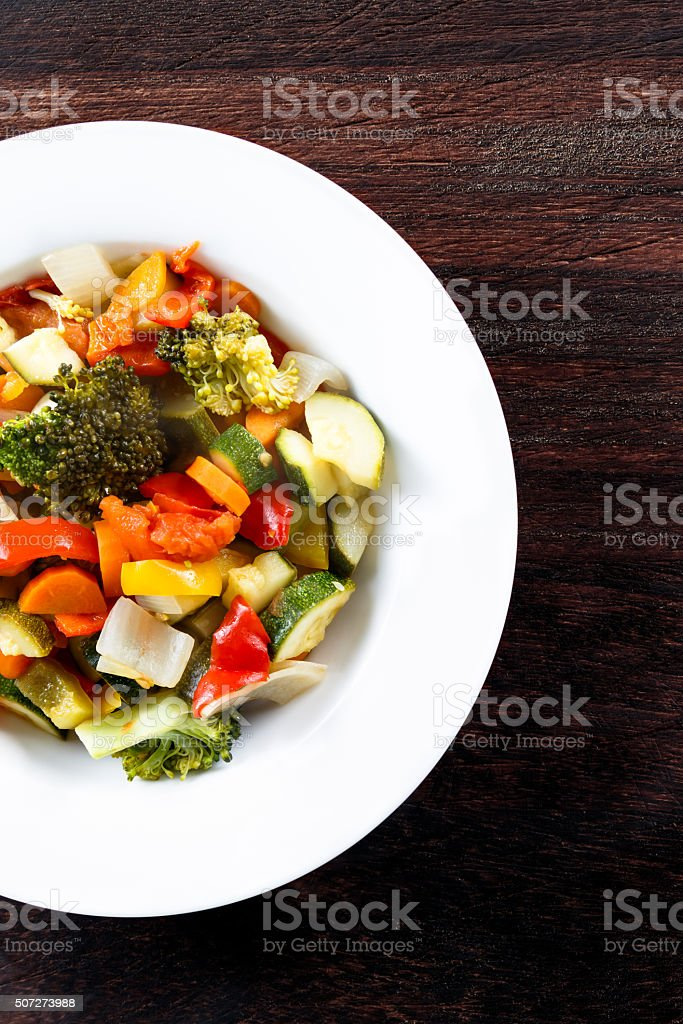 Roasted Vegetables Tomatoes, Carrots, Peppers, Courgettes, brocoli, onion on plates. stock photo