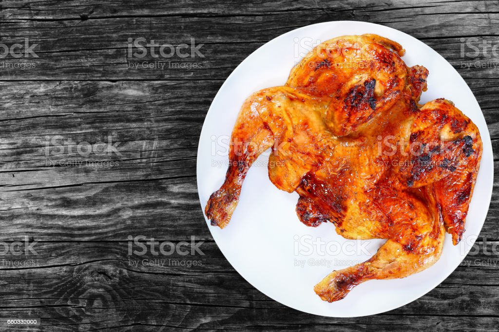 roasted whole chicken on white plate, top view stock photo