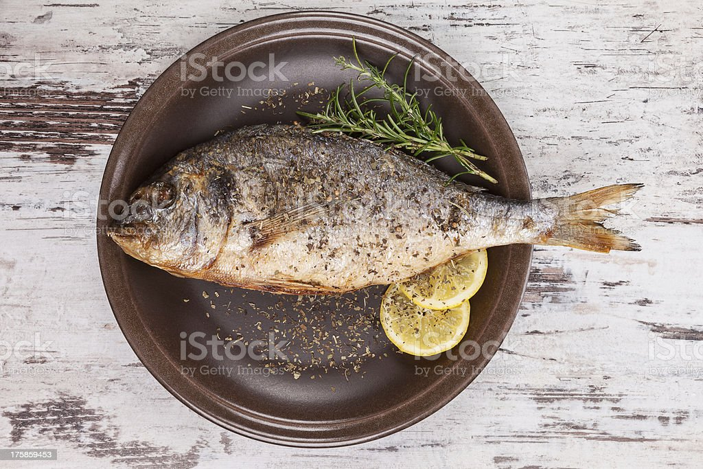 Roasted whole fish with lemon and spices on a brown plate stock photo