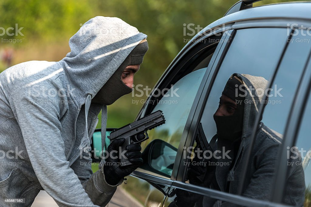 Robber pointing a gun at a driver stock photo