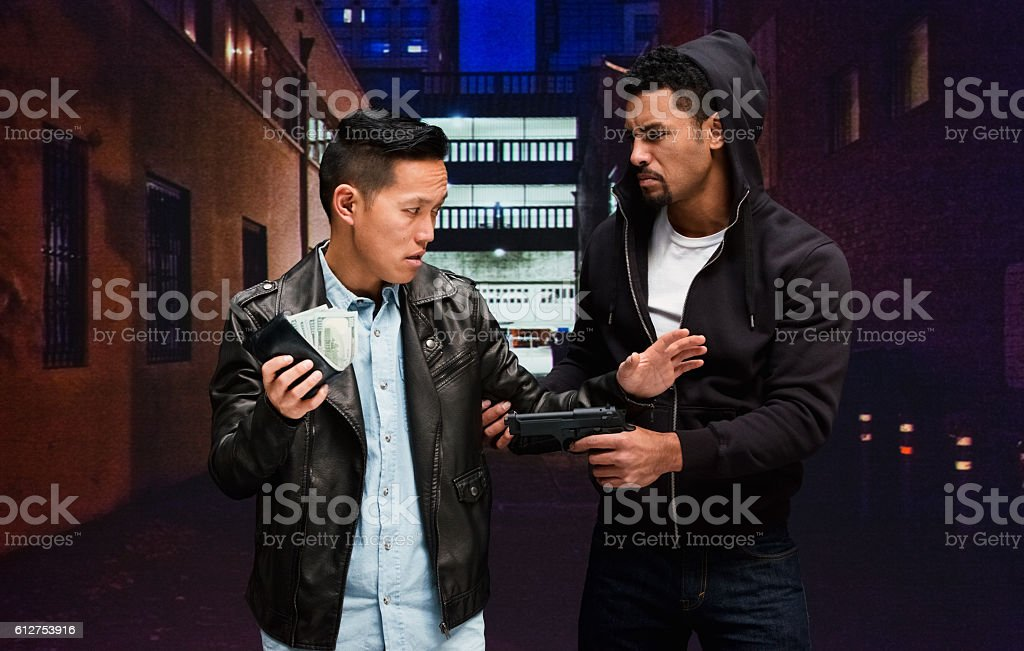 Robber robbing from man at night in the city stock photo