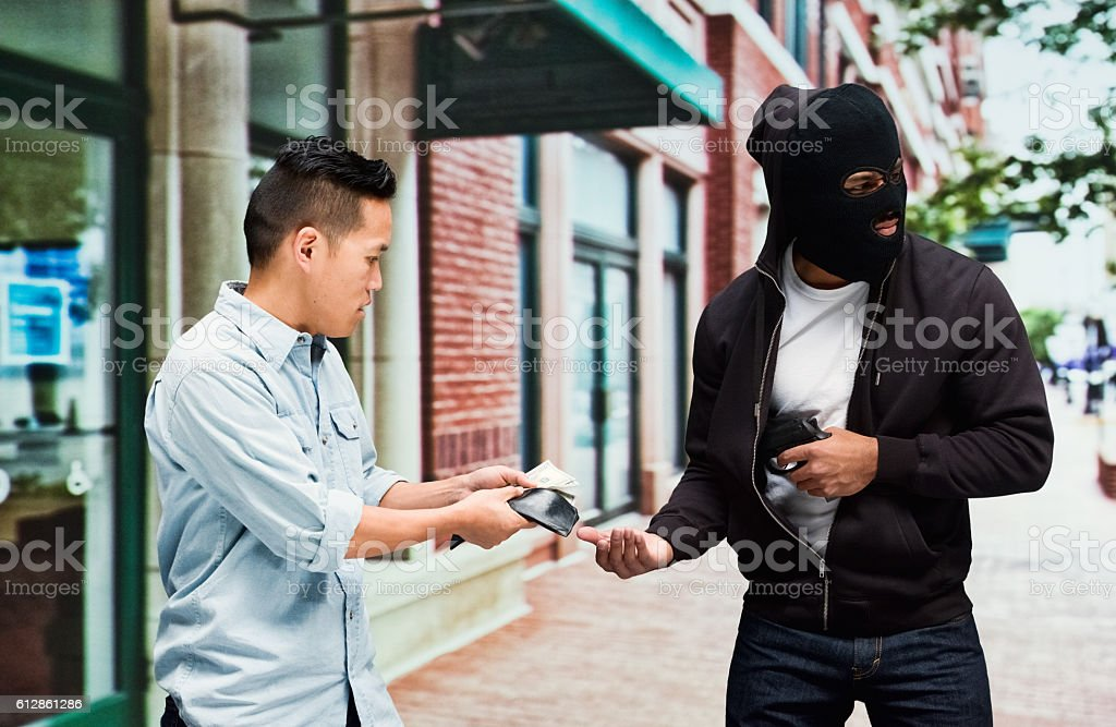 Robber robbing from man outdoors stock photo