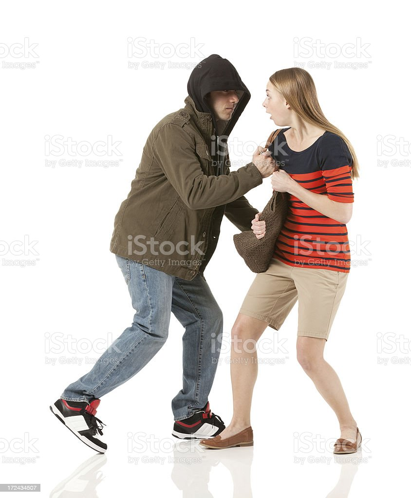 Robber snatching a bag from woman stock photo