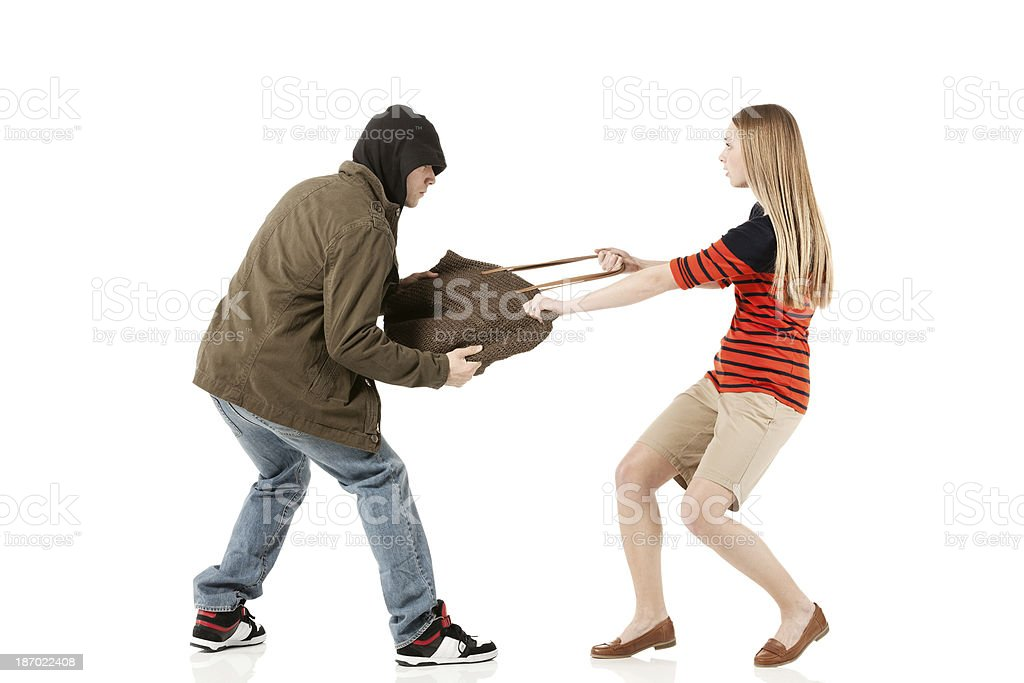 Robber snatching a bag from woman royalty-free stock photo