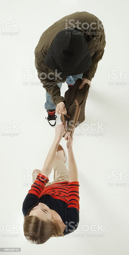 Robber snatching bag from woman stock photo