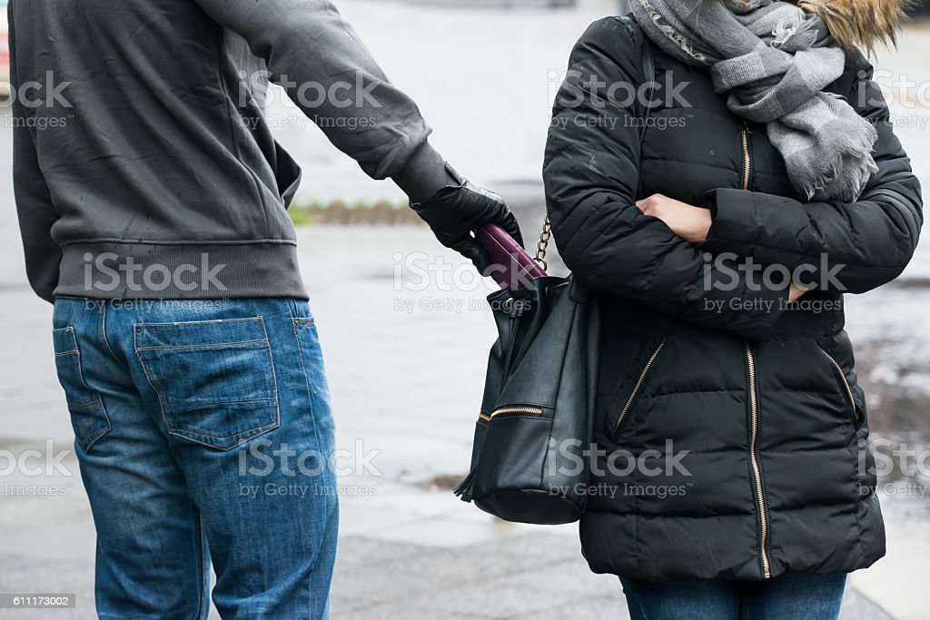 Robber Stealing Clutch From Woman's Jacket On Street stock photo