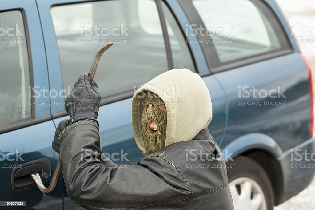 Robber with a crowbar near the car door royalty-free stock photo