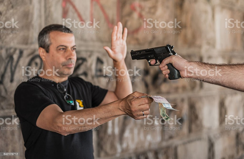 Robber with a gun taking money from victim stock photo