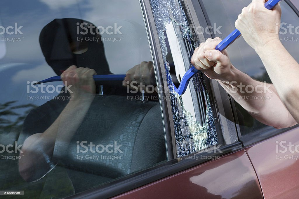 Robber with crowbar smashing glass stock photo