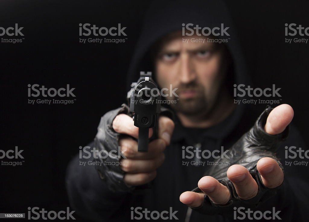 Robber with gun holding out hand stock photo