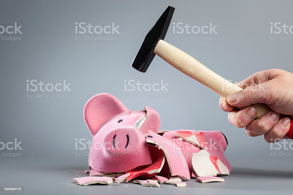 Robbing piggy bank with hammer stock photo
