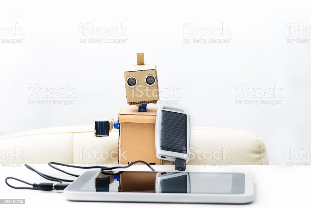 Robot holds a solar battery connected to the tablet stock photo