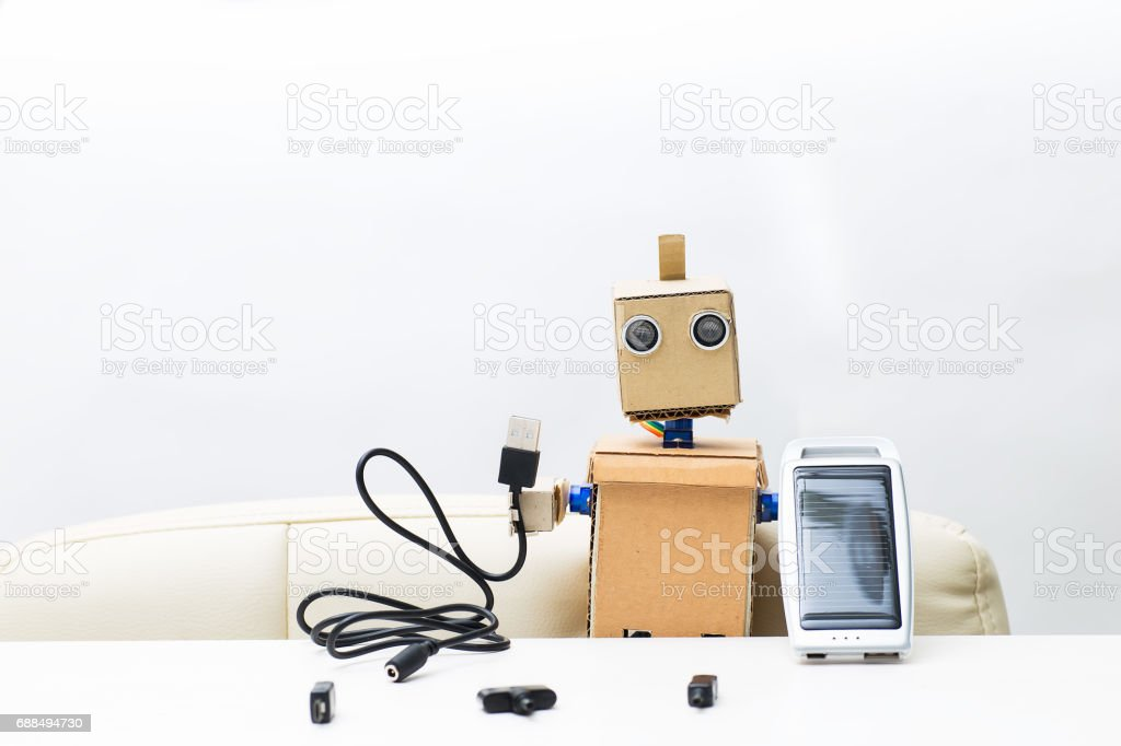 Robot in hand holds solar battery and wire to it stock photo