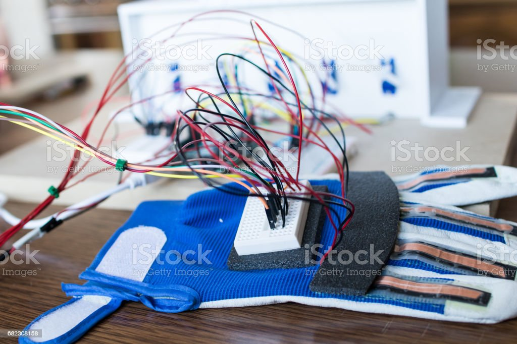 Robotic hand controlled by servomotors and glove with bending sensors. stock photo