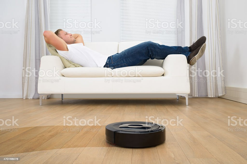 Robotic vacuum cleaner in front of a man relaxing on sofa stock photo