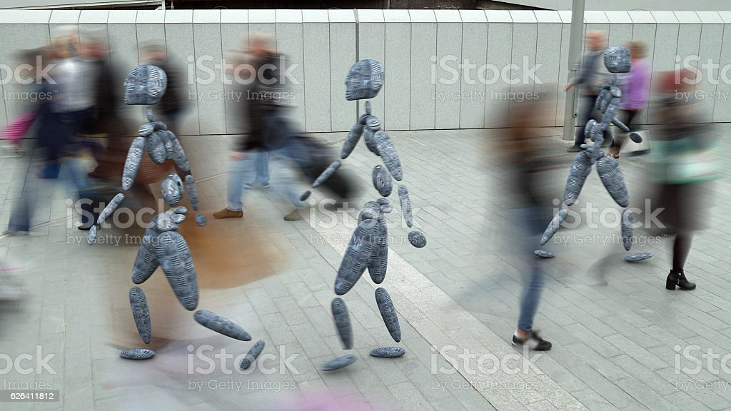 Robots and people in an urban setting. stock photo