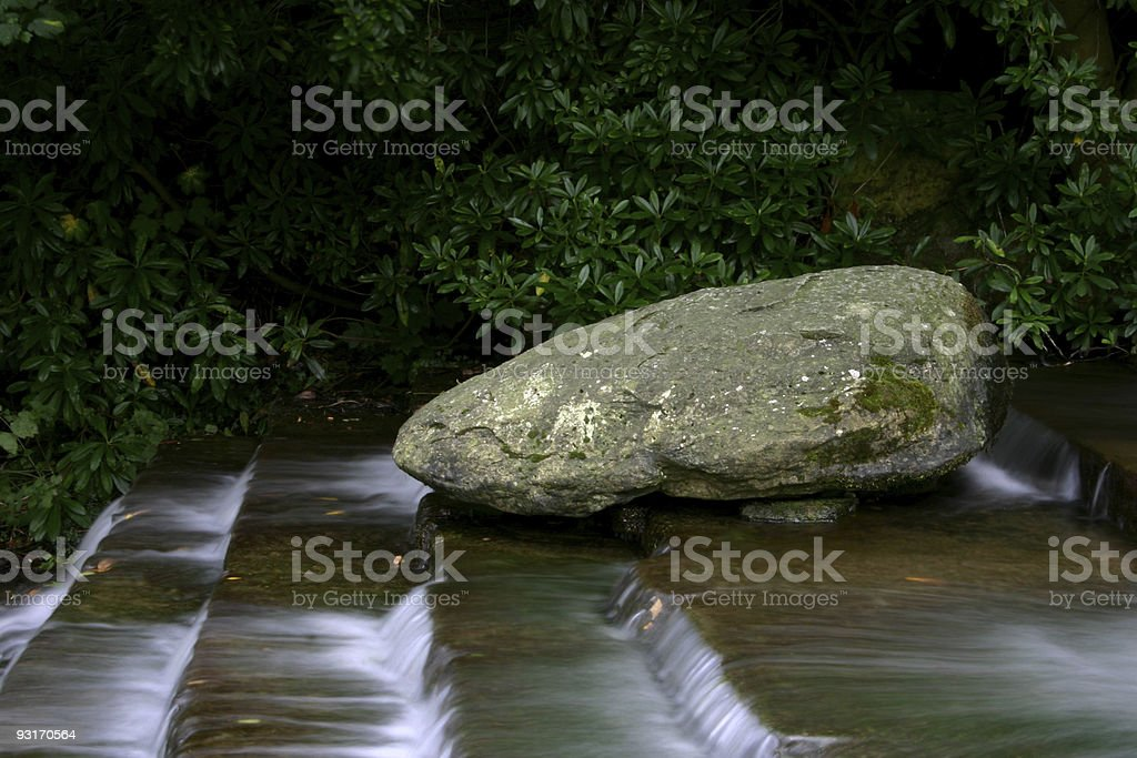 rock against falling rapids : a metaphor for resistance stock photo