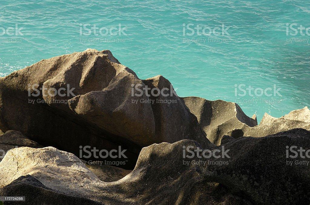 Rock and green sea at Anse Patates royalty-free stock photo
