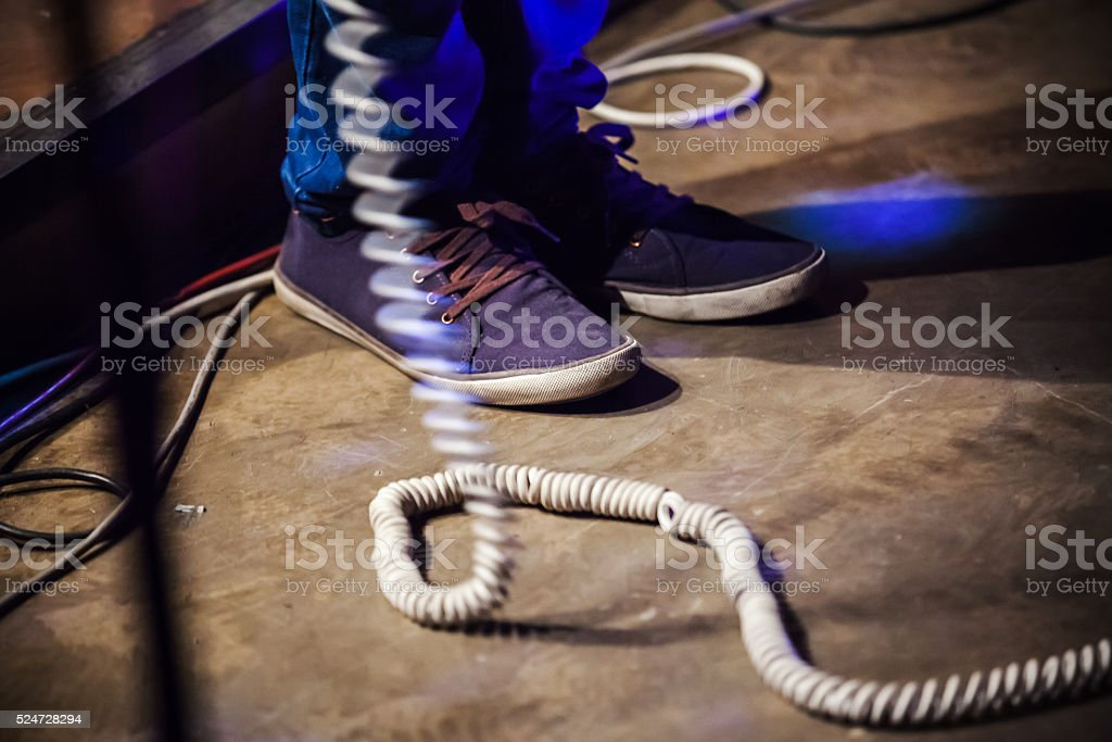 Rock and roll theme. Feet of bass guitar player stock photo
