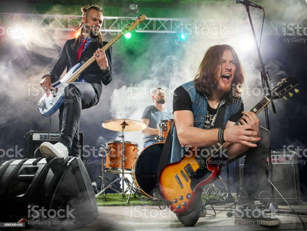 Rock band performs on stage. Guitarist, bass guitar and drums. The...