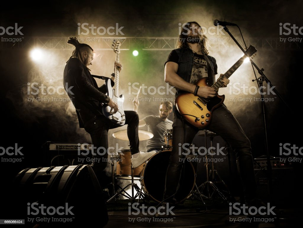 Rock band performs on stage. stock photo