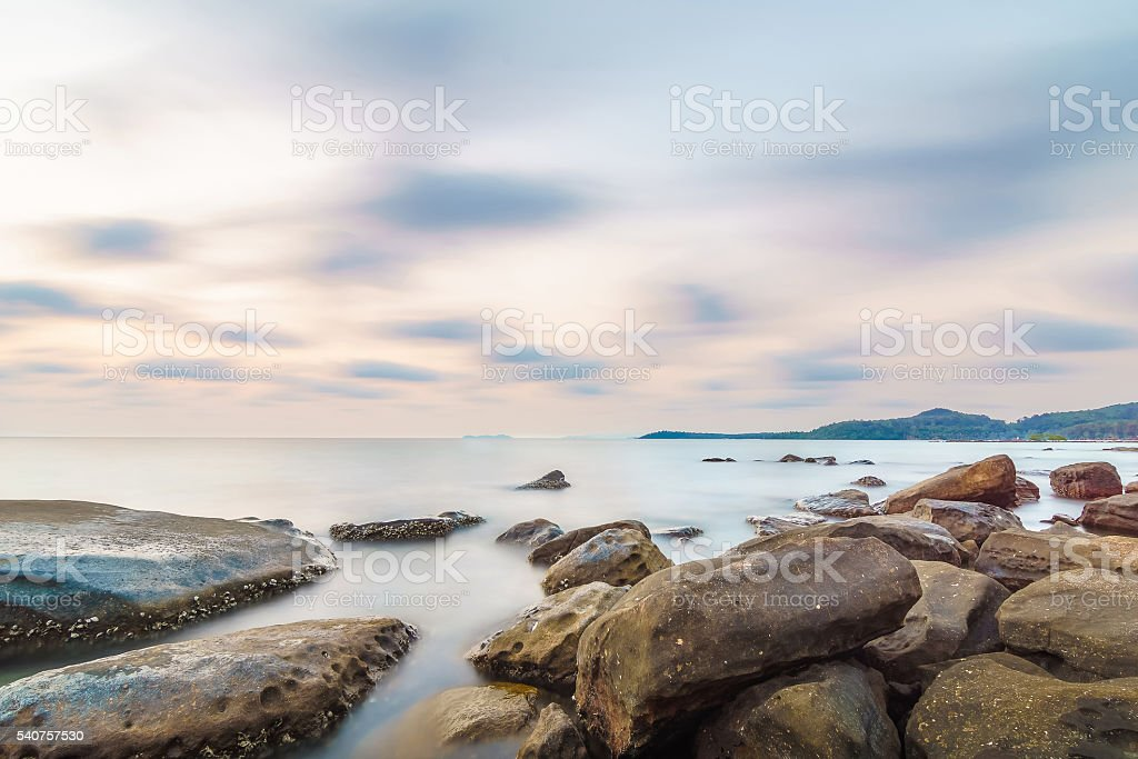 Rock beach at small island and smoothe clouds stock photo