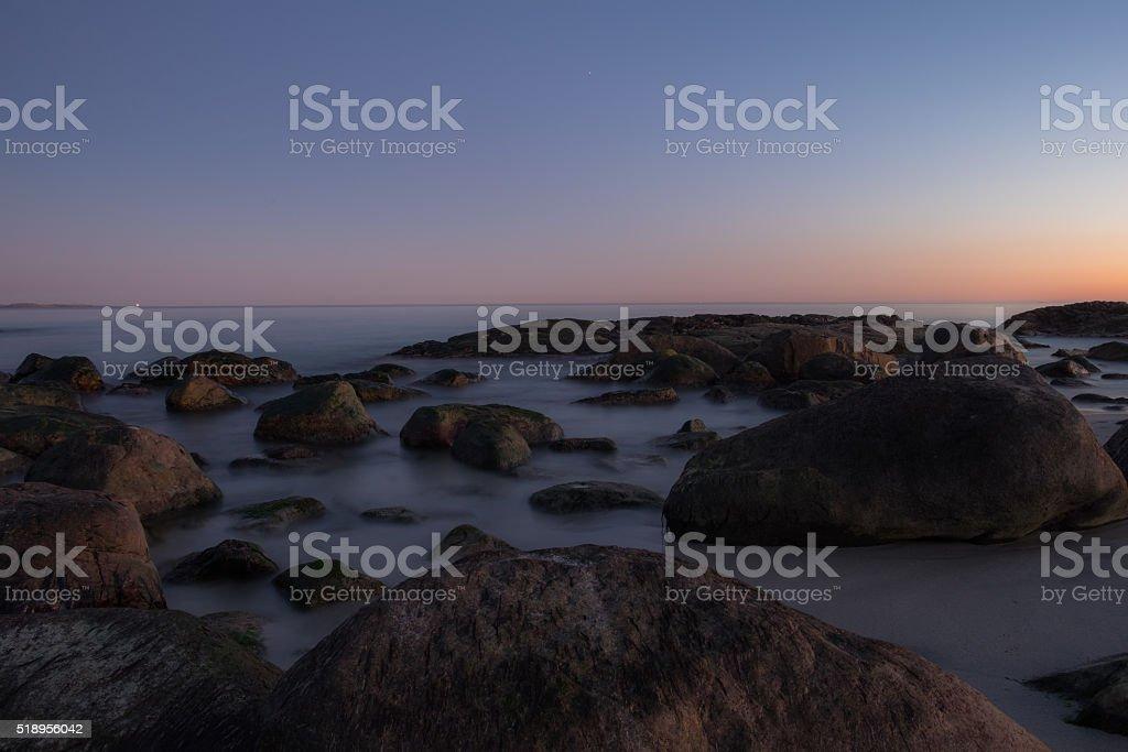 Rock beach sunset stock photo
