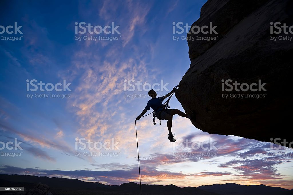 Rock climber against an evening sky stock photo