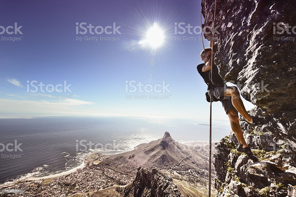 Rock climber against steep cliff stock photo