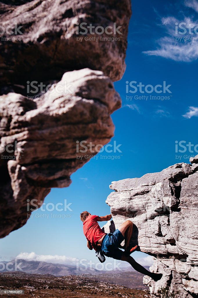 Rock climber almost on top of boulder in extreme outdoors stock photo