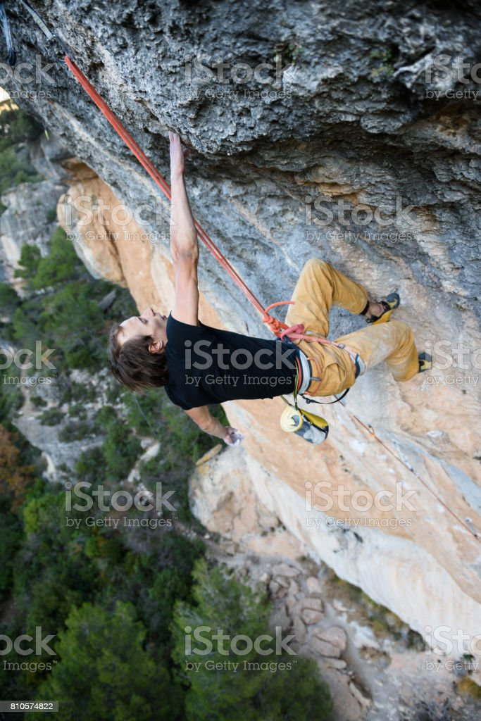 Rock climber ascending a challenging cliff. Extreme sport climbing. Freedom, risk, challenge, success. Sport and active stock photo