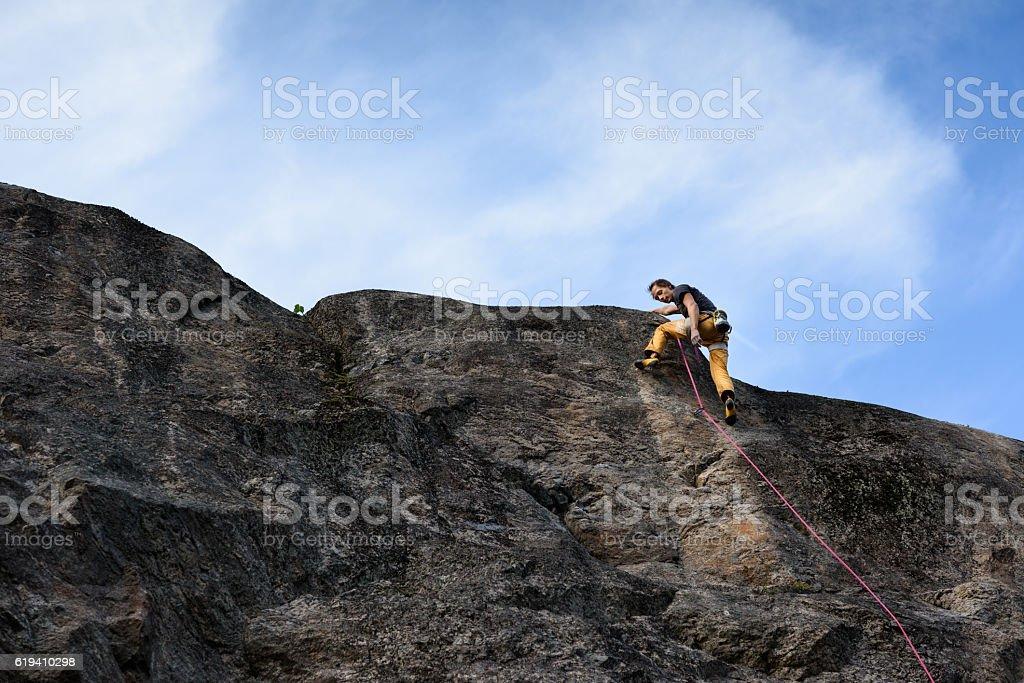 Rock climber, ascending the top. stock photo